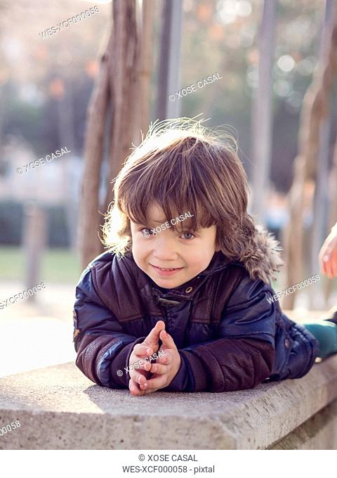Portrait of smiling little boy lying on a bench