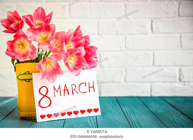 Bouquet of tulips in rain boots on wood table. Woman's day. 8 March. Spring holiday concept