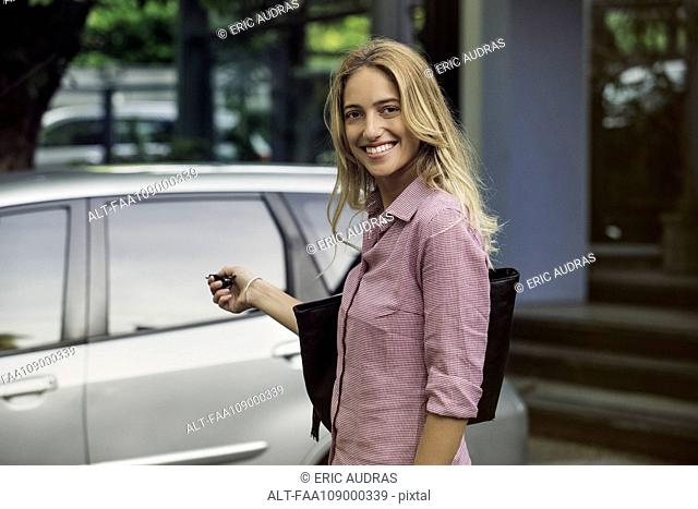 Woman approaching car with key in hand, smiling over shoulder