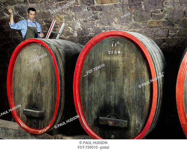 A vintner tests red wine from a barrel