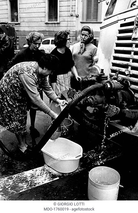 Women queuing to get water. Some women with buckets and jerry cans, gathered around a firemen's tank truck; they are queuing for water and talking to each other