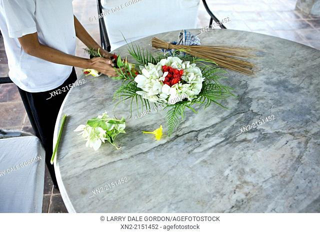 A man arranges orchids and other flowers into a bouquet in Ubud, Bali, Indonesia