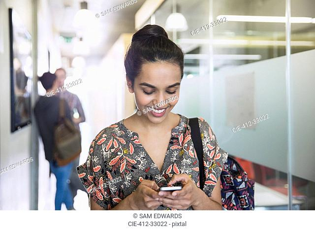 Smiling female college student texting in corridor