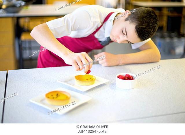 Focused male high school student plating dessert in home economics class