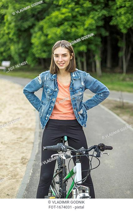 Smiling portrait of woman with hands on hip sitting on bicycle at road in park