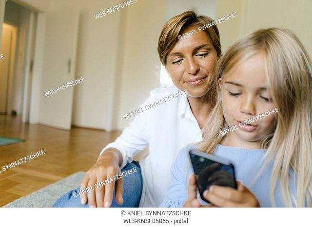Mother and daughter looking at smartphone together