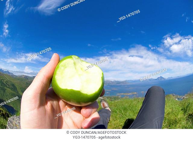 Hand of hiker holding partially eaten apple on mountain top, Lofoten islands, Norway