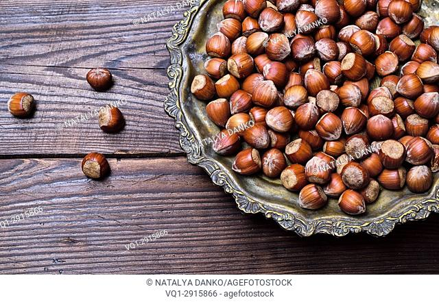 Hazelnuts on an iron plate, empty space on the left