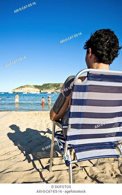 Man relaxing in deckchair on beach at Cala Mongo
