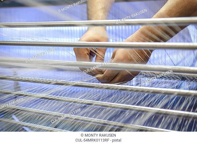 Worker adjusting threads on loom