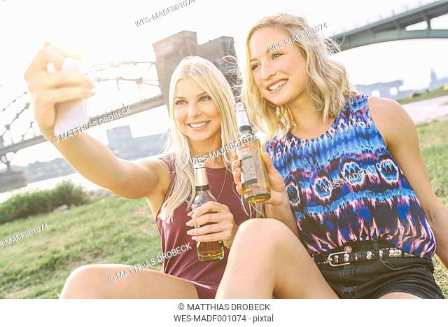 Two smiling young women with beer bottles taking a selfie at riverbank
