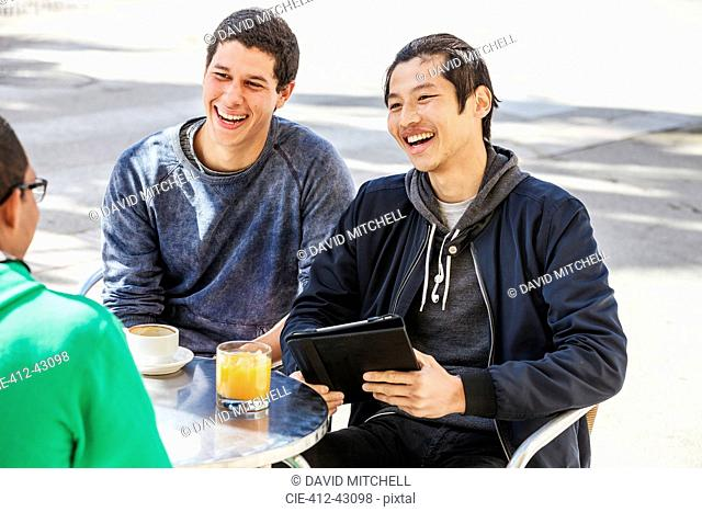 Male friends with digital tablet laughing at sidewalk cafe