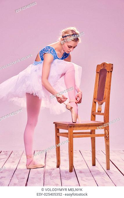 Professional ballerina putting on her ballet shoes on the wooden chair on a pink background