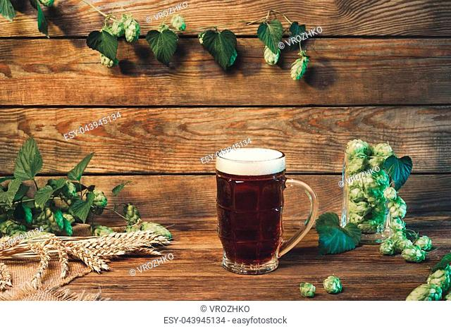 Beer glass with lager, dark lager, brown ale, malt and stout beer on table in bar or pub, still life with wooden background, vintage filter