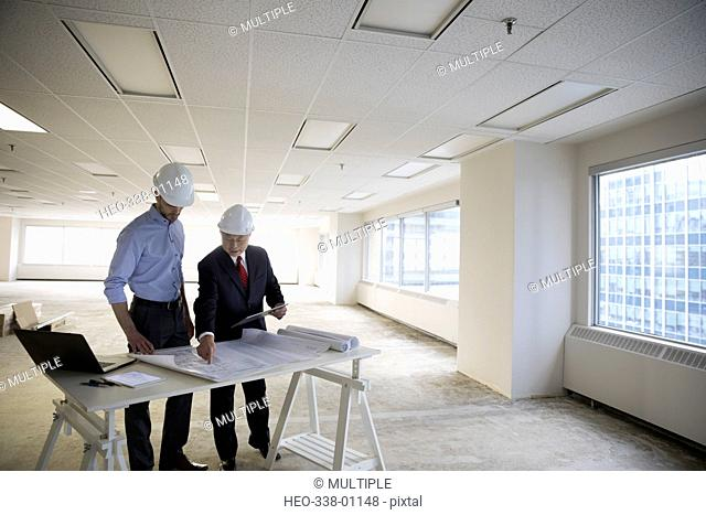 Architect and contractor reviewing blueprints in unfinished, empty urban office