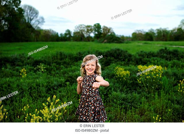 Portrait of girl with wavy blond hair punching in field