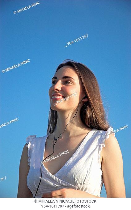 Smiling young woman wearing earphones outdoors