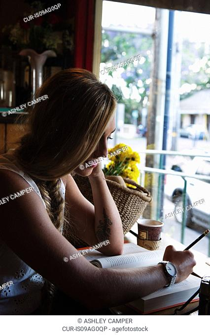 Young woman writing on book in cafe