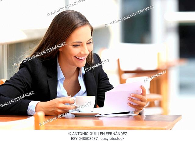 Single happy businesswoman reading a letter sitting in a coffee shop