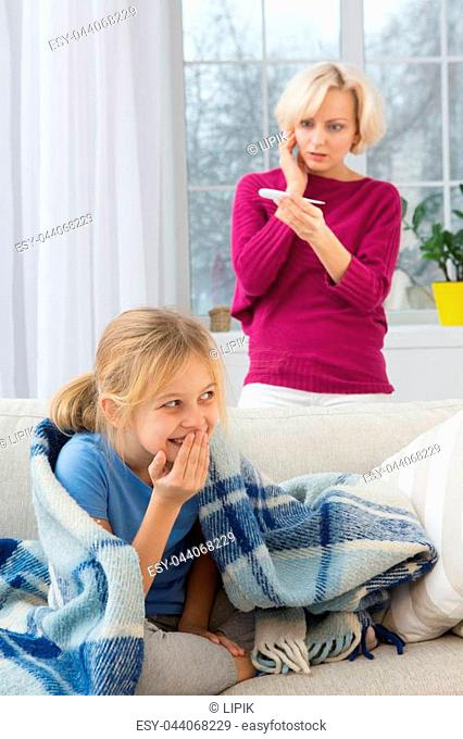 Little sick girl under blanket smiling, concerned mom on background. When child is sick mom stays at home