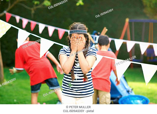 Girl covering her eyes for hide and seek with brothers in garden
