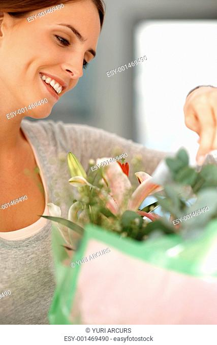 Closeup of beautiful young woman with a flower bouquet reading a love note - Indoor