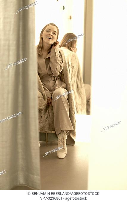 Fashionable woman in fitting room, in Munich, Germany