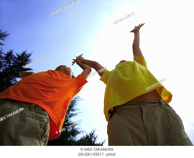 Low angle view of two boys with their arms raised