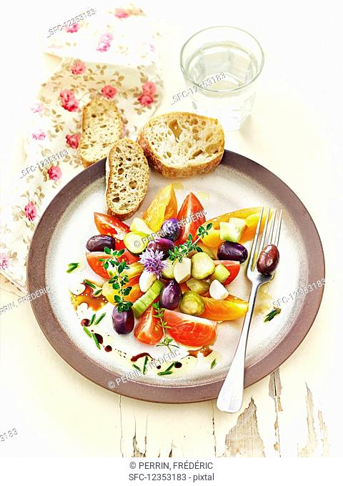 Lacto fermented tomatoes, cucumbers, and olives served with herbs and garlic bread