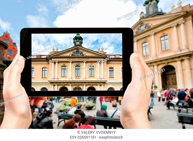 travel concept - tourist photographs facade of swedish academy palace on stortorget square in stockholm on tablet pc