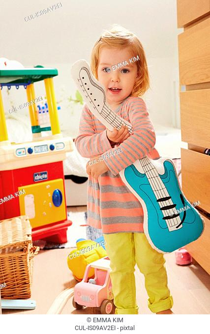Portrait of female toddler in playroom holding toy guitar