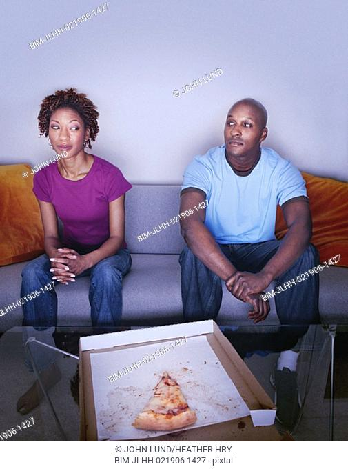 African couple and last slice of pizza