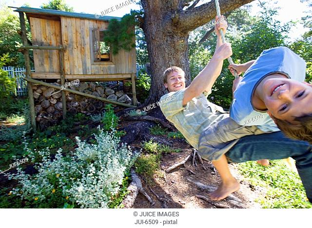 Father and son 8-10 swinging on garden rope swing near tree house, smiling, portrait wide angle