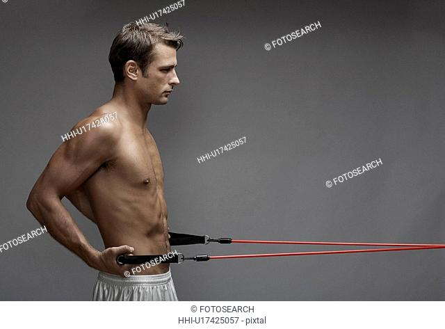 Mid adult man weight training with cable