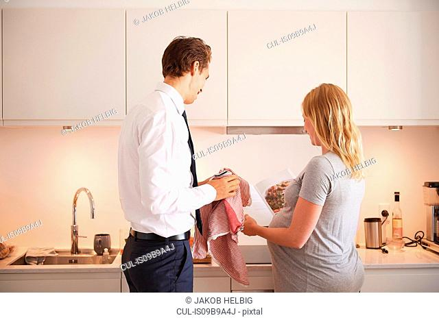 Pregnant couple in kitchen looking at cook book