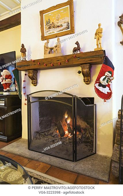 Lit wood burning fireplace decorated with Christmas stockings inside an old circa 1886 Canadiana cottage style home