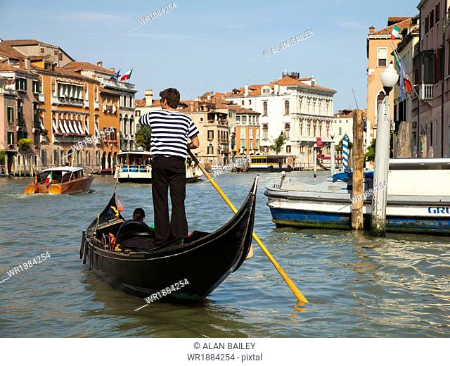Italy, Venice, Young woman traveling in gondola on canal