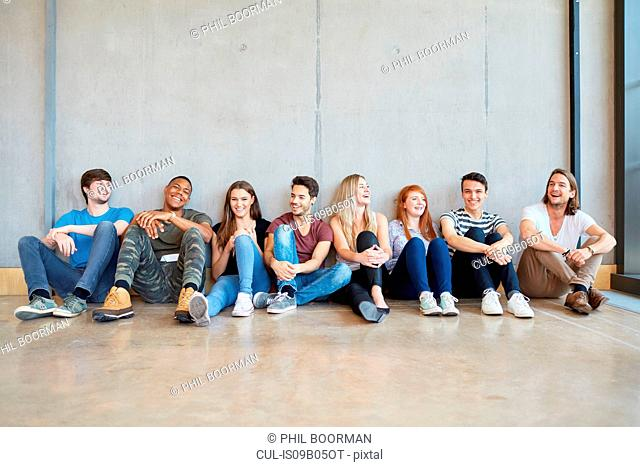 Group portrait of male and female students sitting on floor in a row at higher education college