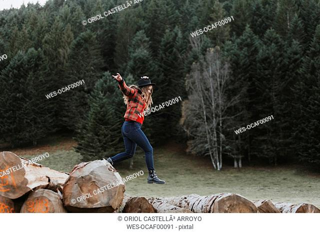 Young woman balancing on logs