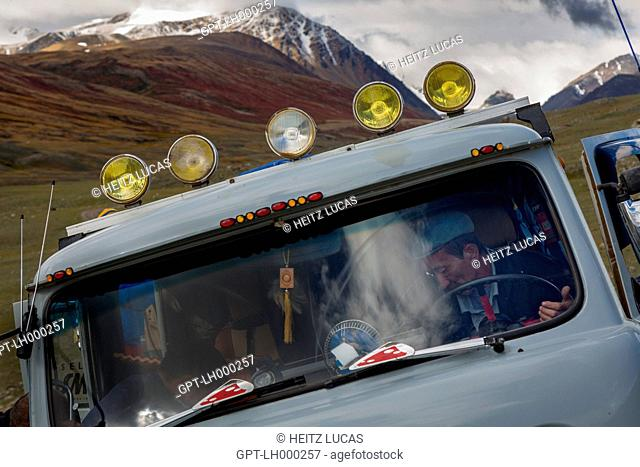 KAZAKH DRIVER OF A RUSSIAN JEEP WITH MECHANICAL PROBLEMS, REDDISH HILLS AND SNOW-COVERED SUMMITS IN THE DISTANCE, TAVAN BOGD MASSIF, ALTAI, BAYAN-OLGII PROVINCE