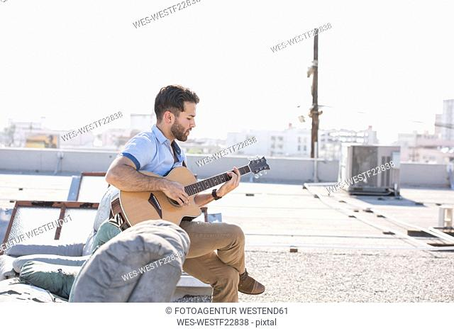 Young man on rooftop sitting on sofa and playing guitar