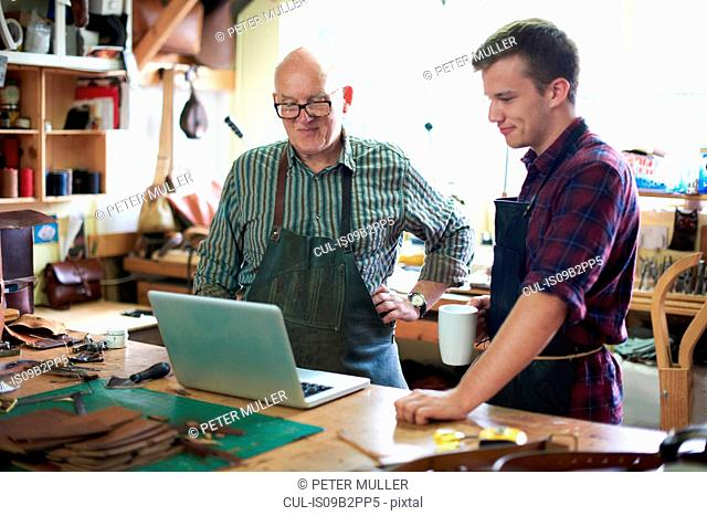 Two male workers in leather workshop, looking at laptop