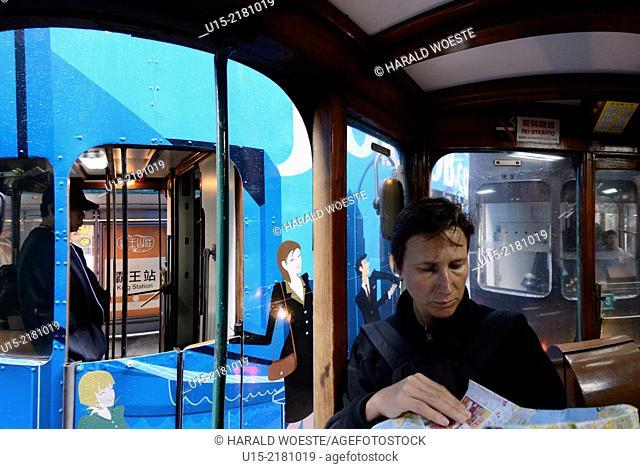 Hong Kong, China, Asia. European female tourist reading a map while on a tram on Hong Kong Island