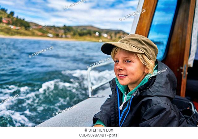 Boy looking out from motor boat at sea, Puno, Peru