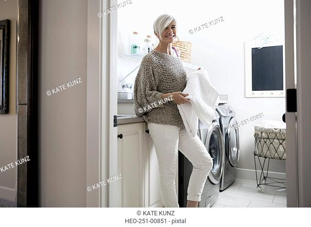 Portrait smiling woman folding towels in laundry room