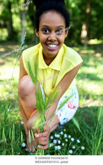 Portrait of smiling young woman picking grasses