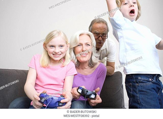 Grandparents and grandchildren 8-9 playing video game, portrait