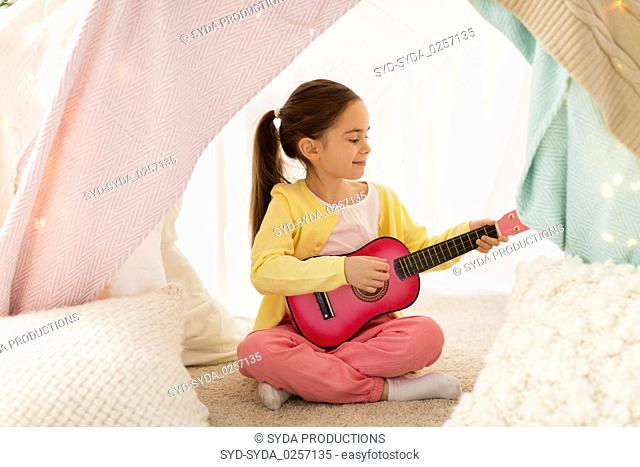 girl playing toy guitar in kids tent at home