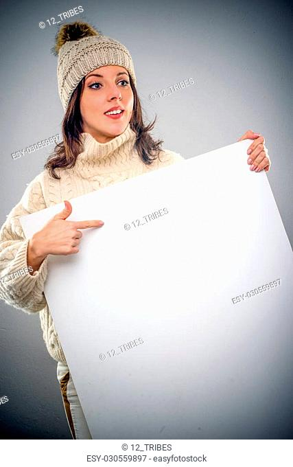 Pretty young woman wearing a turtleneck sweater and knitted woollen cap pointing to a blank white sign with copy space that she is holding in front of her chest