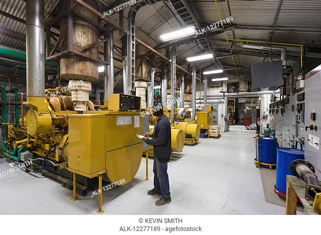 A male Hispanic worker inspects a yellow diesel generator inside an electrical power plant, Prudhoe Bay, Arctic Alaska, USA, Summer